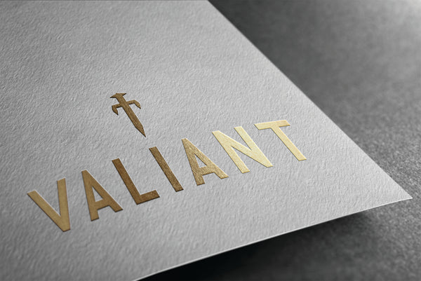 Valiant new logo in gold foil on a piece of paper.