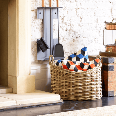 Lifestyle image of Valiant Dassels Log Basket sitting next to a fireplace with Carlisle Wall Mounted Companion Set