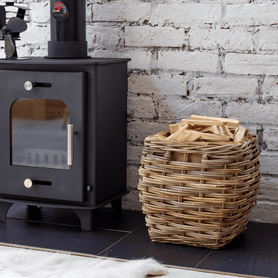 Lifestyle image of Valiant lined Kelshall Log Basket next to wood burning stove with Premium 4 Stove Fan