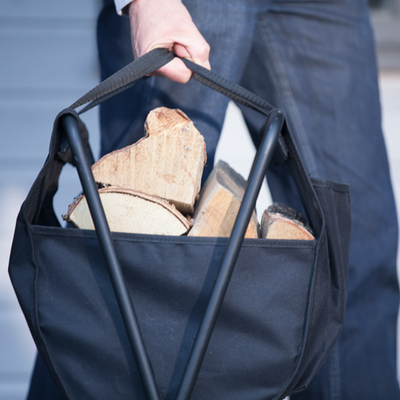 Lifestyle image of man carrying the Valiant Carry & Store with logs in