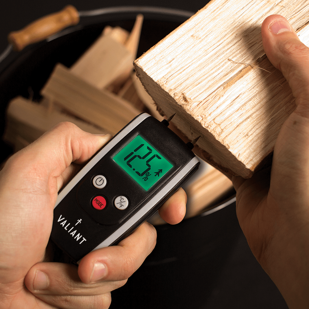Lifestyle image of Valiant Colour Change Moisture Meter in use, testing is firewood is seasoned