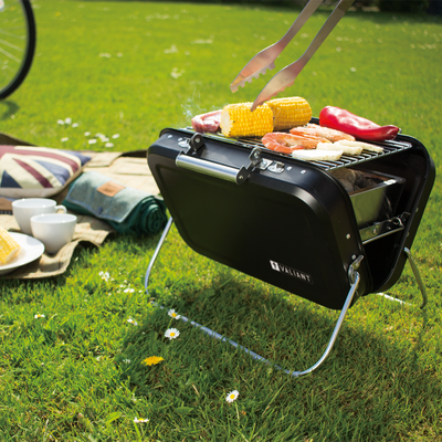 Valiant Nomad portable BBQ, lit with hot charcoal and cooking an assortment of BBQ food.