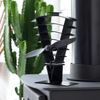 A photo of the Vanquish 250 Fan sitting on a stove top in a conservatory with a green cactus behind.