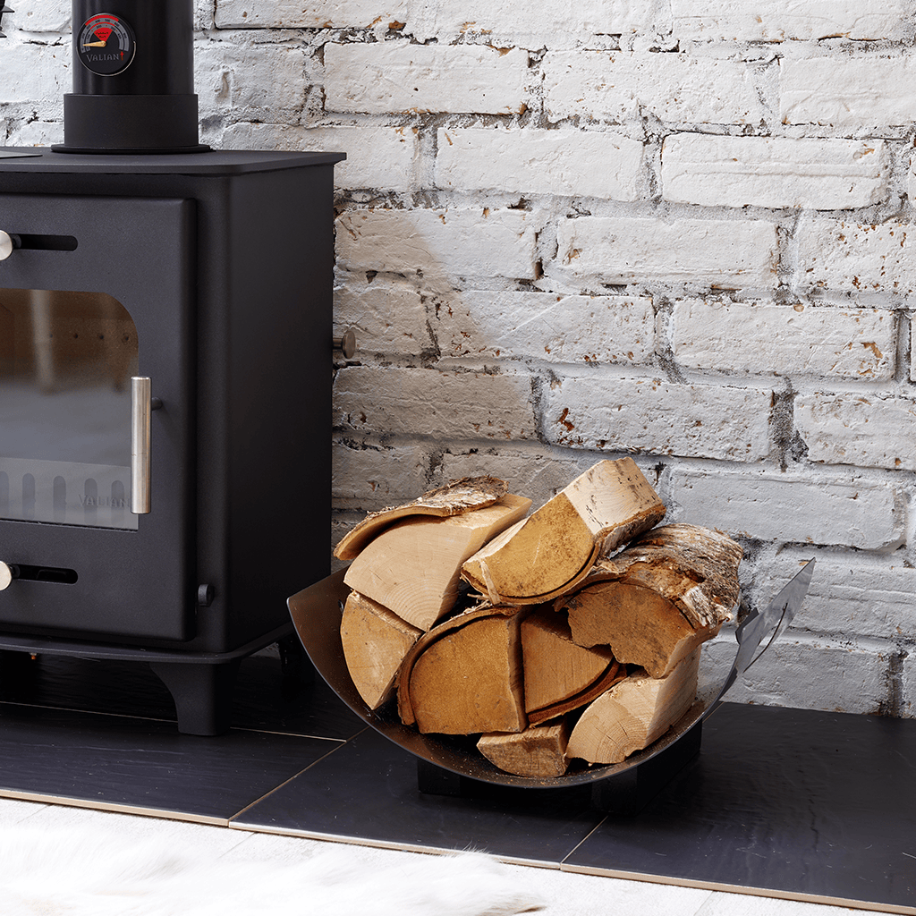 Lifestyle image of Valiant York metal Log Stand filled with logs sitting on hearth next to a stove