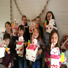 children showing completed craft projects