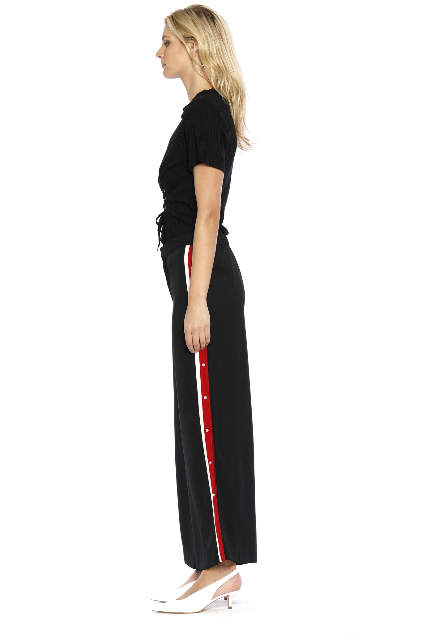 Side view of Maxine Pant, black retro pants with buttons on the side and a red stripe outlined with white borders on both sides, 100% Polyester and Machine-washable.