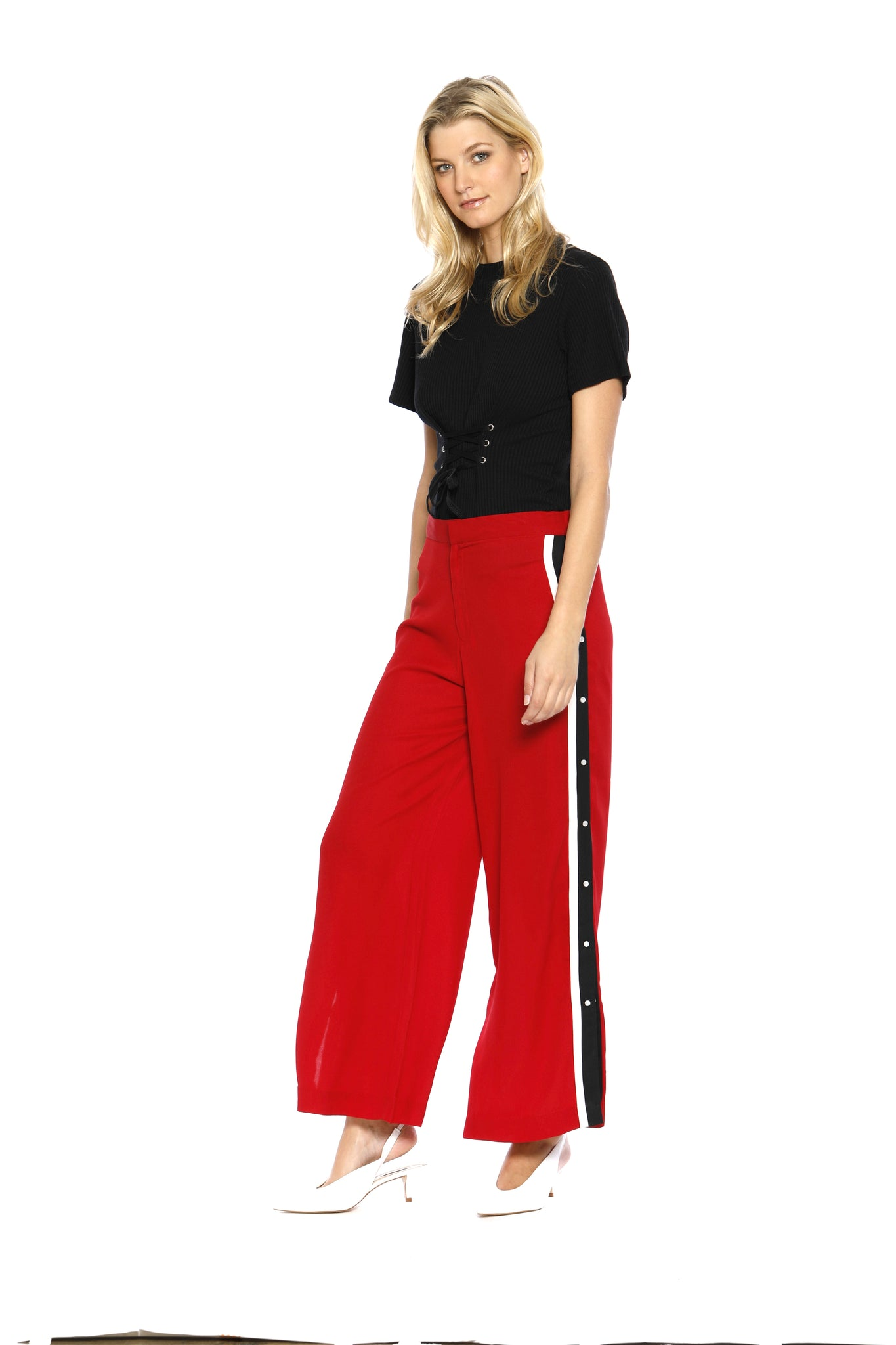 Front view (pose) of Maxine Pant, red retro pants with buttons on the side and a black stripe outlined with white borders on both sides, 100% Polyester and Machine-washable.