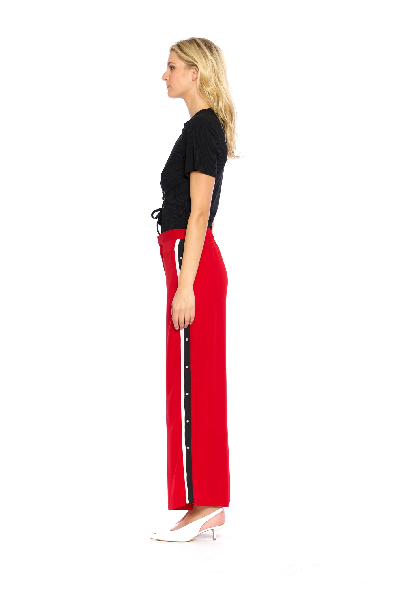 Side view of Maxine Pant, red retro pants with buttons on the side and a black stripe outlined with white borders on both sides, 100% Polyester and Machine-washable.