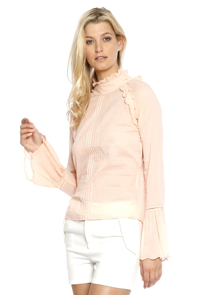 Front view (pose) of Camille Top, pale blush pink long-sleeved illusion top with bell sleeves and a flowery collar. 100% Cotton Voile and Machine-washable.