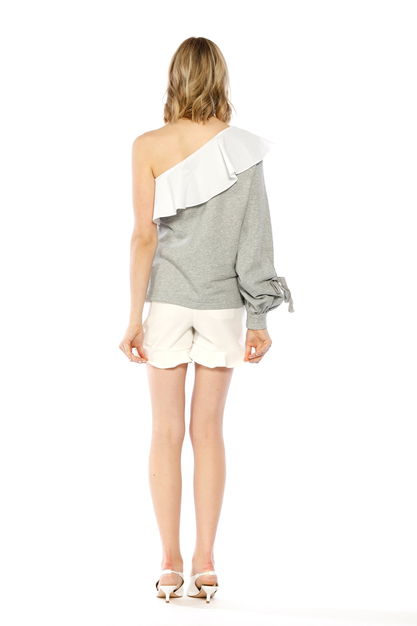 Back view of Marge Top, heather grey one-shouldered top with a large ruffled collar and a bishop sleeve adorned with a small tie. 87.6% Cotton and 12.4% Spandex - and Machine-washable.