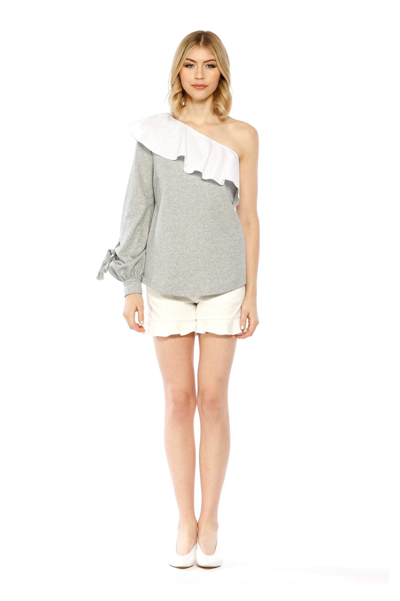 Front view of Marge Top, heather grey one-shouldered top with a large ruffled collar and a bishop sleeve adorned with a small tie. 87.6% Cotton and 12.4% Spandex - and Machine-washable.