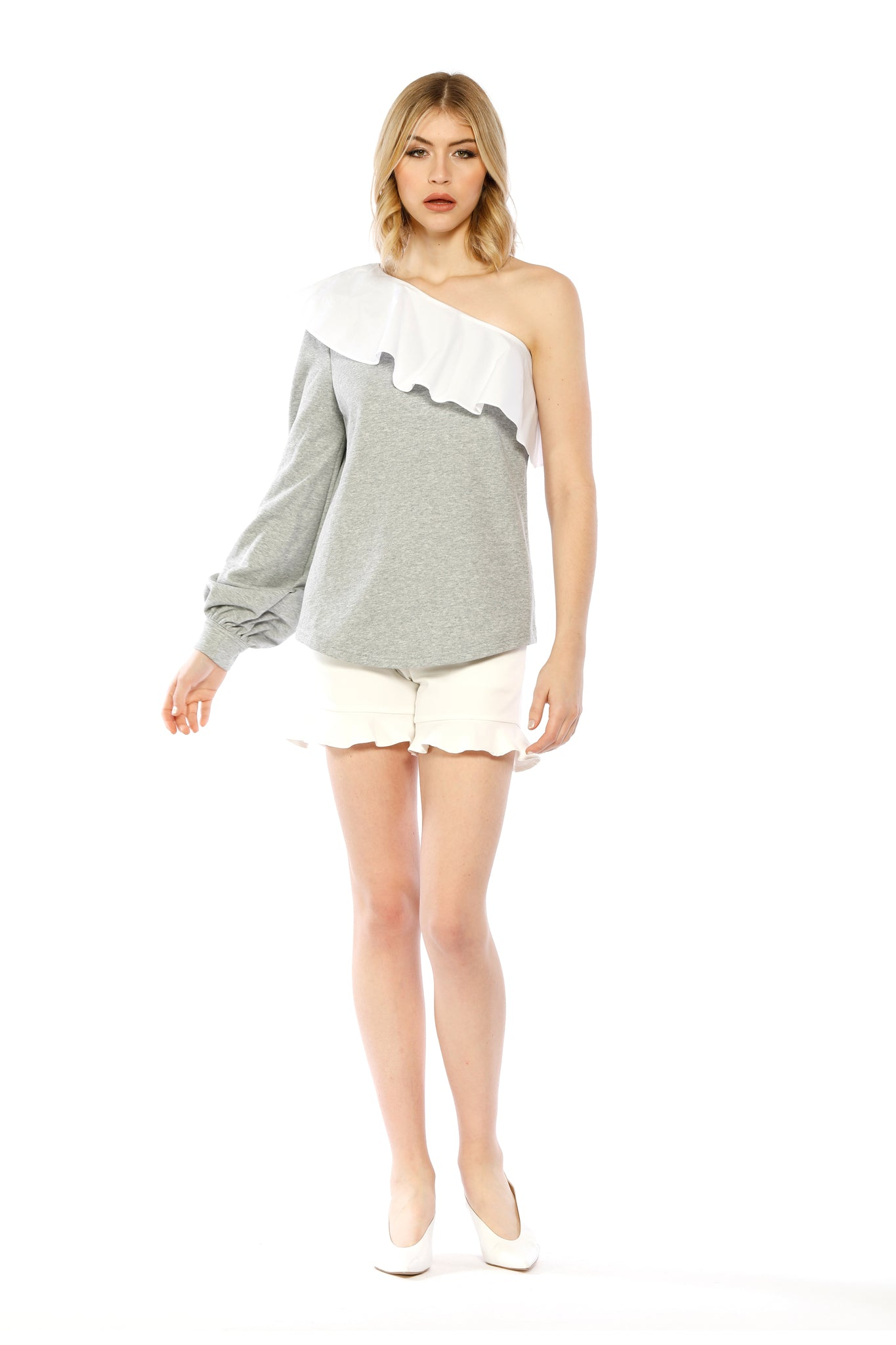 Front view (pose) of Marge Top, heather grey one-shouldered top with a large ruffled collar and a bishop sleeve adorned with a small tie. 87.6% Cotton and 12.4% Spandex - and Machine-washable.