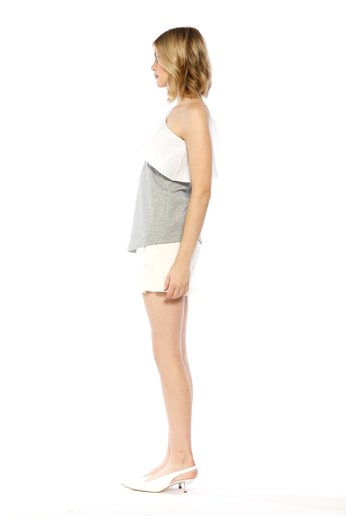 Side view of Marge Top, heather grey one-shouldered top with a large ruffled collar and a bishop sleeve adorned with a small tie. 87.6% Cotton and 12.4% Spandex - and Machine-washable.