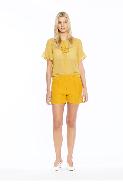 Front view of Bonnie Top, mustard swiss dot short-sleeved illusion top with cascading ruffles along the neckline. 100% Polyester and Machine-washable.