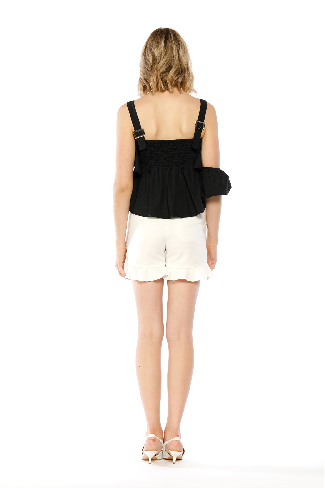 Back view of Kim Top, black adjustable strap tank top with ruffled collar, flowing side frill, and one batwing sleeve. 100% Cotton and Machine-washable.