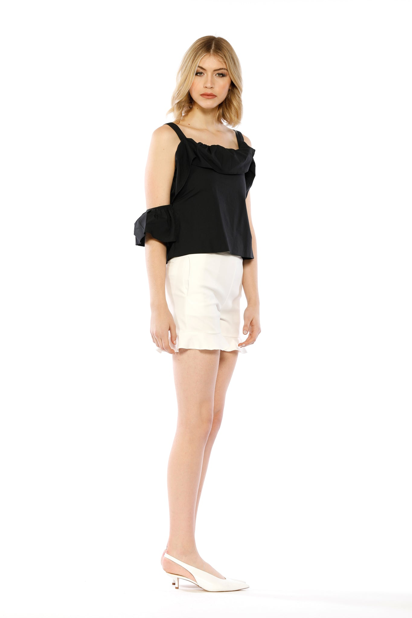 Front view (pose) of Kim Top, black adjustable strap tank top with ruffled collar, flowing side frill, and one batwing sleeve. 100% Cotton and Machine-washable.