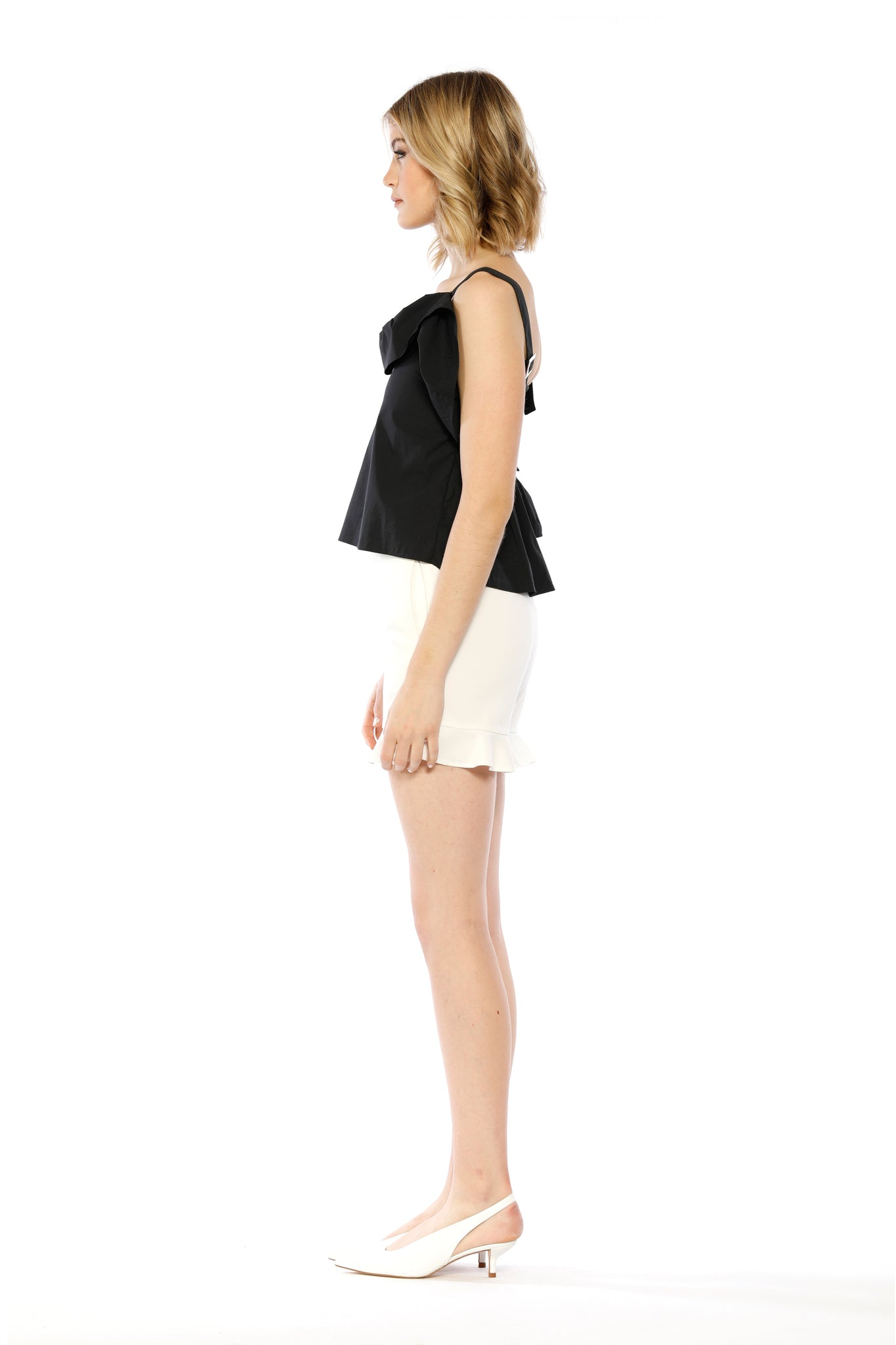 Side view of Kim Top, black adjustable strap tank top with ruffled collar, flowing side frill, and one batwing sleeve. 100% Cotton and Machine-washable.