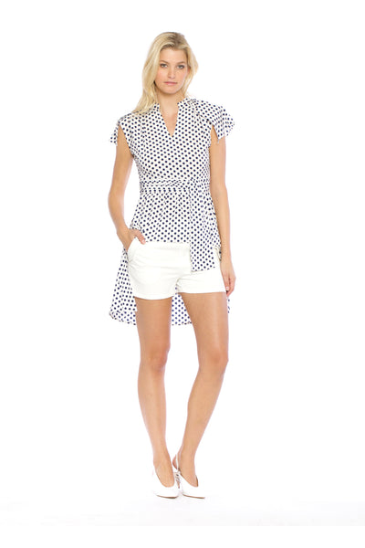 Front view (pose) of Blake Top, blue polka dot high-low top with capped sleeves and a cloth waist tie. 100% Polyester and Machine-washable.