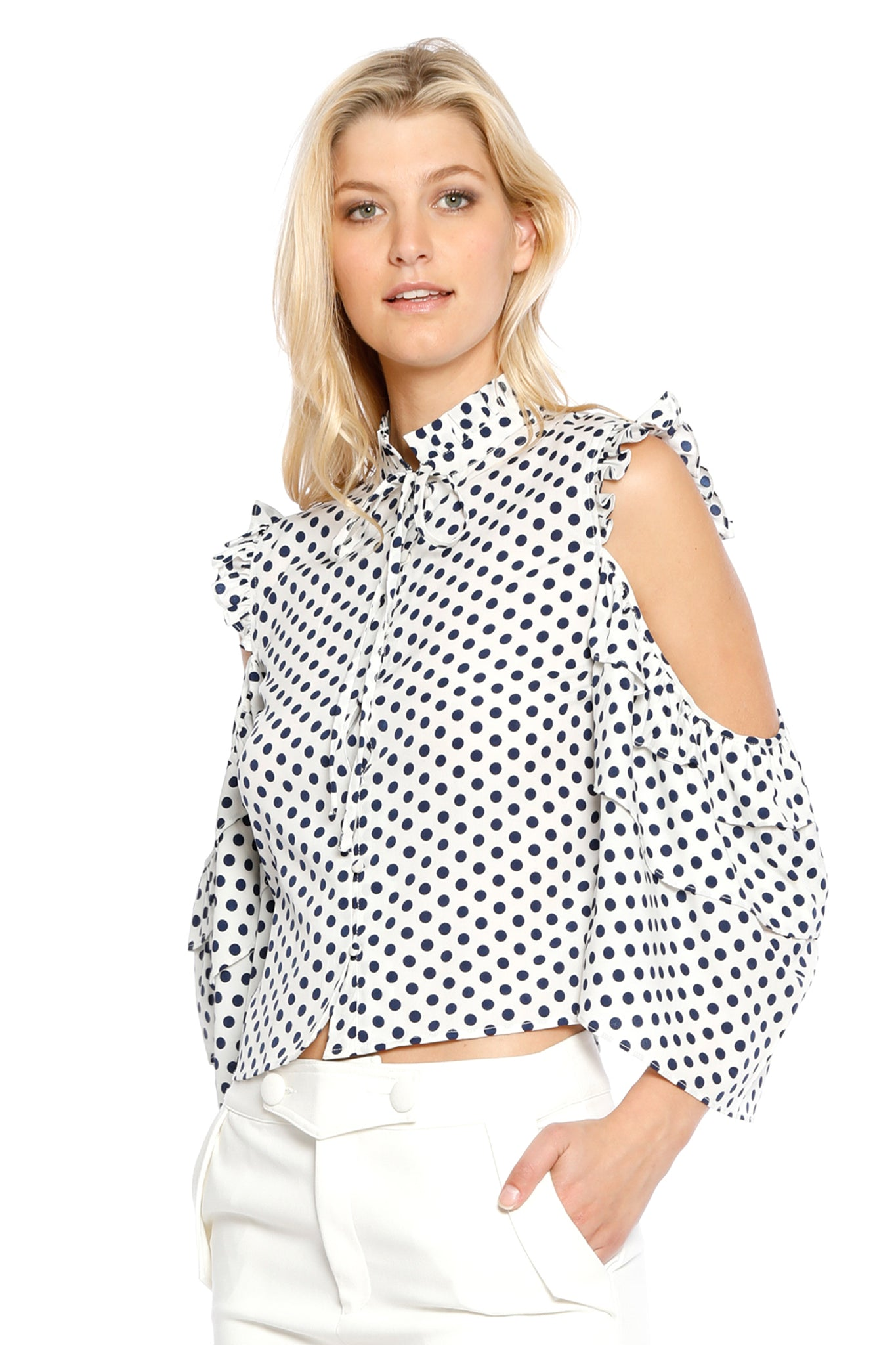Front view (pose) of Silvia Top, blue polka dot top with batwing sleeves, shoulder cuts, and slight ruffles. 100% polyester and machine-washable.