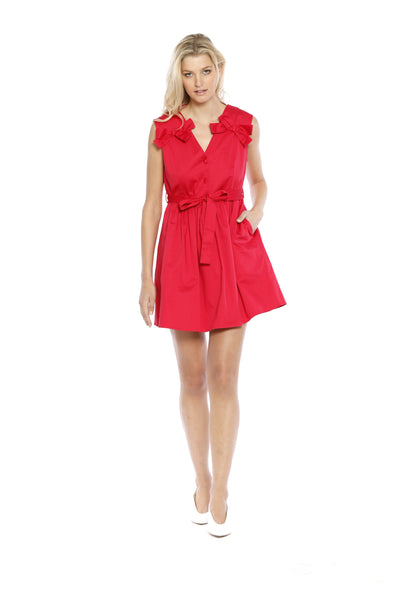 Front view (pose) of Lauren Dress, short, petite red dress with a V-neck cut and three bows - a small one on each shoulder and a larger waist one. 100% Cotton and Machine-washable.