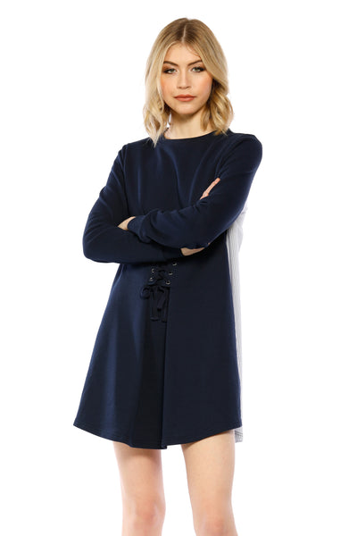Front view (pose) of Anne Dress, short dress with a dark navy front that uses a criss-crossed design and white-striped back with sleeves in the same dark navy color. Front is 87.6% Cotton and 12.4% Spandex, back is 65% Cotton, 32% Nylon, and 3% Spandex - and Machine-washable.