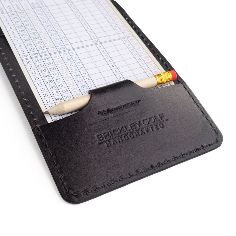 Black leather yardage book cover with scorecard and pencil
