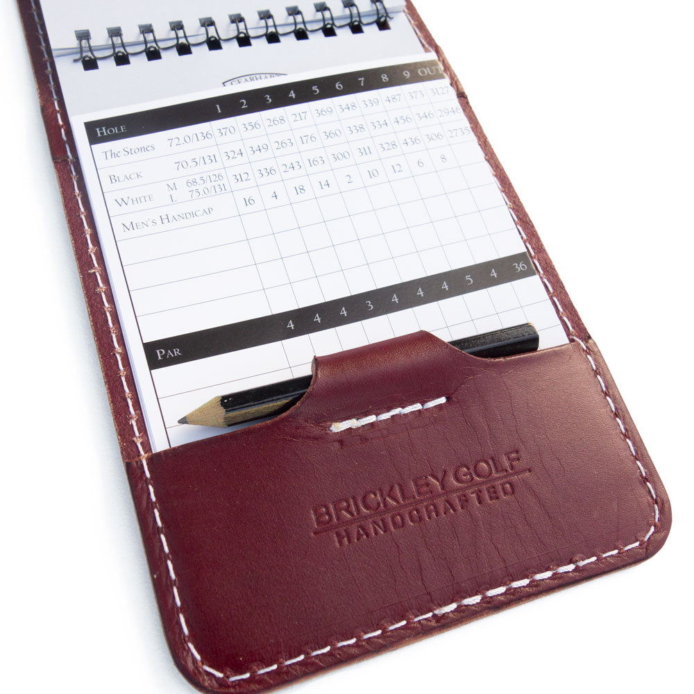 Burgundy leather yardage book cover with scorecard and pencil