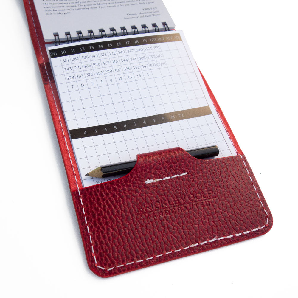 Red pebble yardage book cover with scorecard and pencil