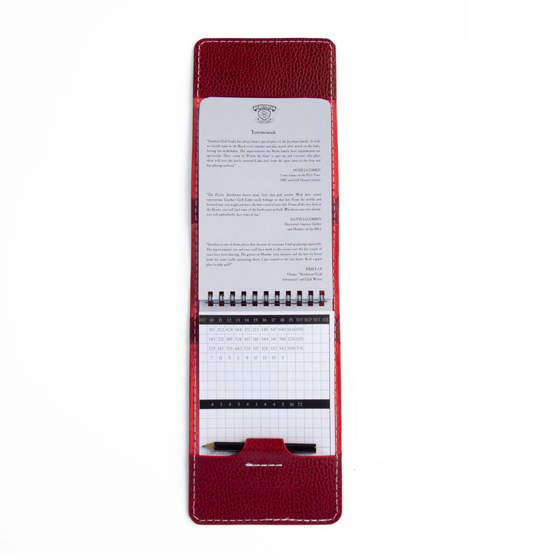 Red pebble yardage book cover open with yardage book and pencil
