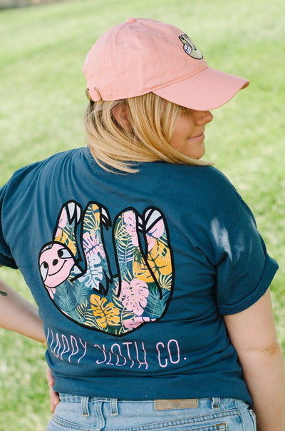Girl facing away from camera with her head turned in a blue, floral sloth tee
