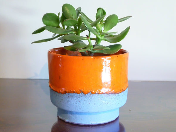 Fernanda indoor plant pot, bright dripping orange on matt blue