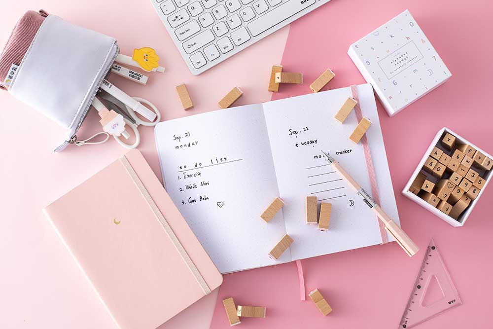 Flat-lay image of an open bullet journal with a pink bullet journal next to it and stamps scattered all over the desk