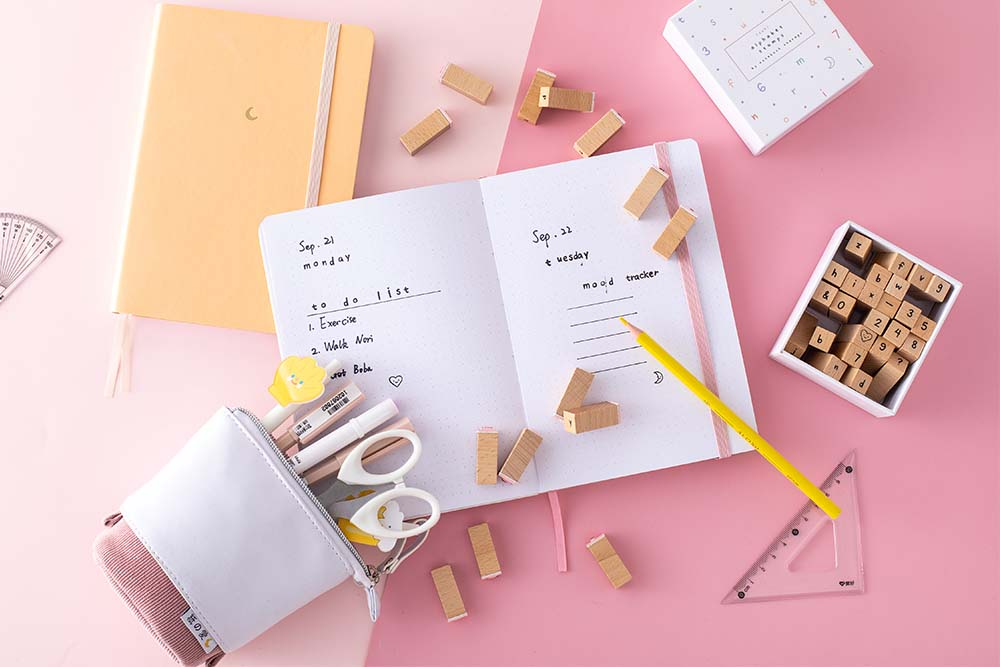 Flat-lay image of an open bullet journal with a yellow bullet journal next to it and stamps scattered all over the desk