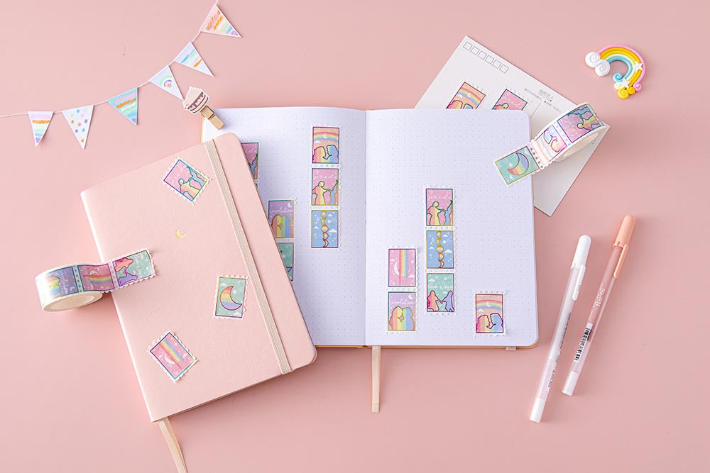 Tsuki Rainbow Pride Washi Tape on open notebook page with pink sakura Tsuki Pastel Edition Bullet Journal and postcard with rainbow and bunting and pens on light pink background