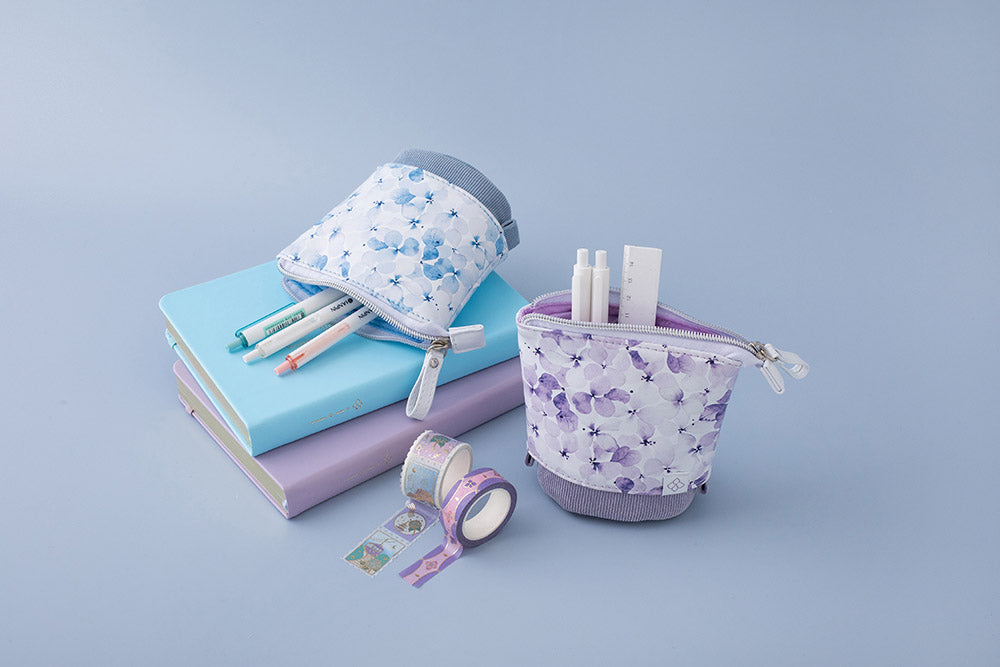 Tsuki Endless Summer Pop-Up pencil cases in petal blue and lilac bloom with pens on stacked Tsuki Endless Summer Bullet journals with Tsuki Endless Summer Washi tapes on light blue backgroun