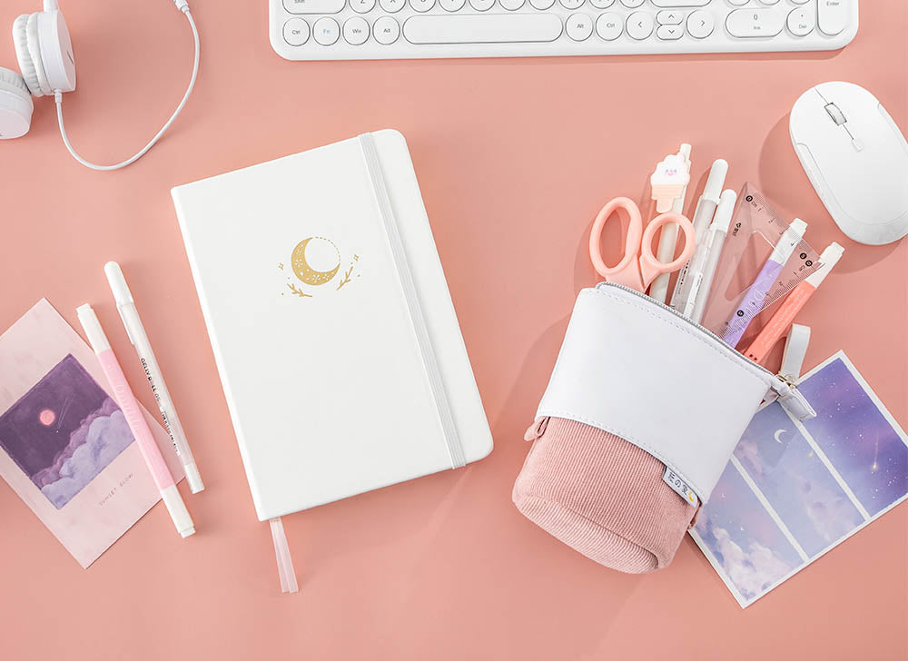 white moon flower bullet journal on pink background next to pink pop up pencil case