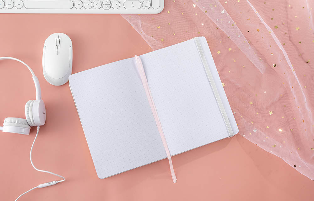 lay flat bullet journal on a pink background