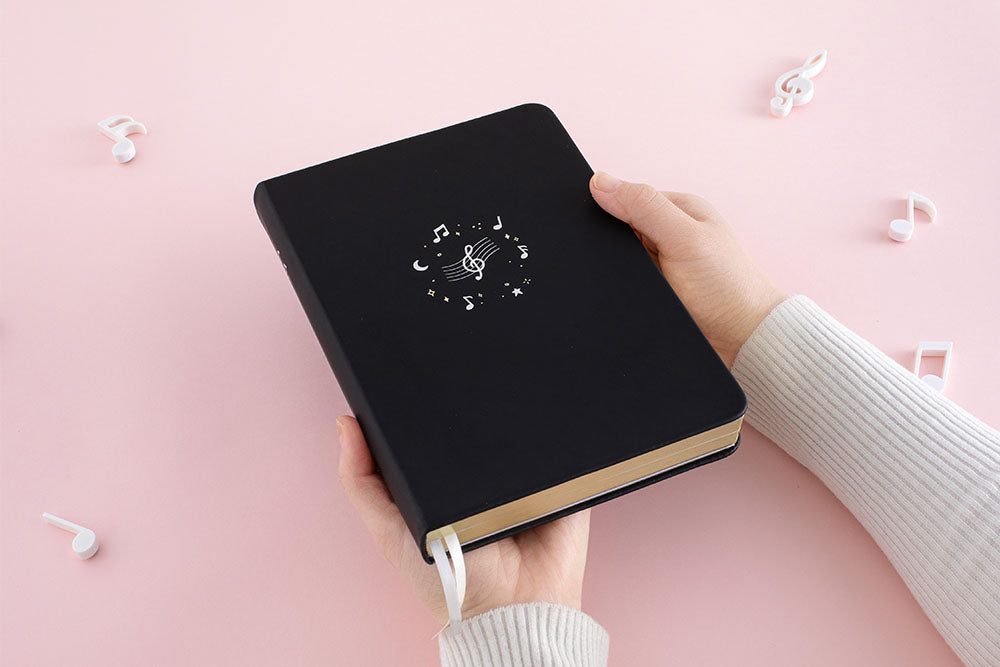 Tsuki Lunar Notes bullet journal in hands image in pink background
