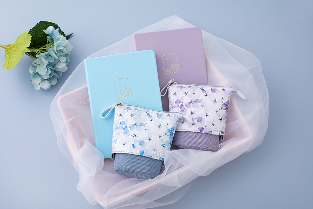 Tsuki Endless Summer Pop-Up pencil cases in petal blue and lilac bloom with Tsuki Endless Summer Bullet journals in basket with netting with blue hydrangea flowers on light blue background