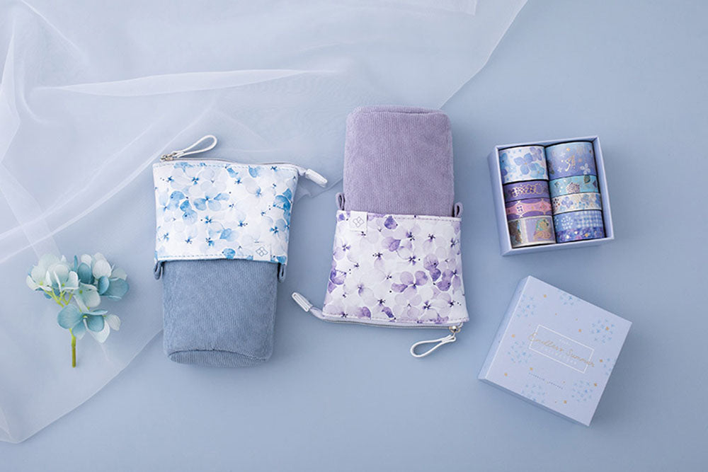 Tsuki Endless Summer Pop-Up pencil cases in petal blue and lilac bloom with Tsuki Endless Summer washi tape set with netting with blue hydrangea flowers on light blue background
