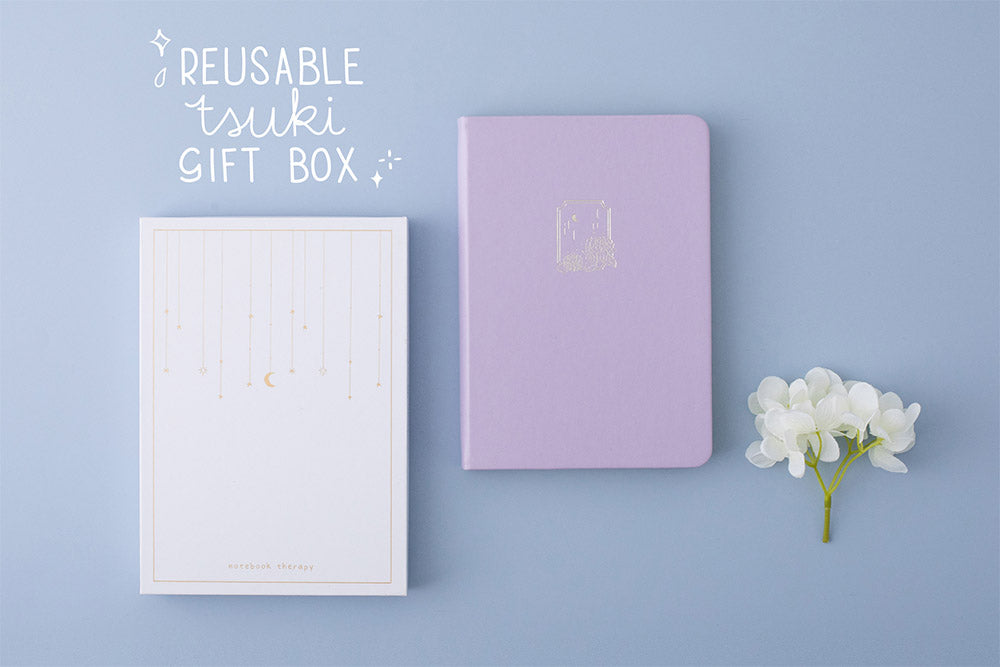 Tsuki Endless Summer Limited Edition Bullet Journal in Lilac Bloom with reusable Tsuki gift box and white hydrangea flowers on light blue background