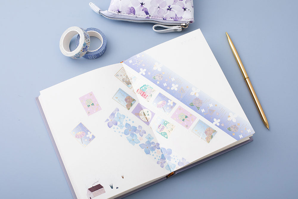 Tsuki Endless Summer Washi Tape Set on open bullet journal page with Tsuki Endless Summer pop-up pencil case in lilac bloom with pen on light blue background