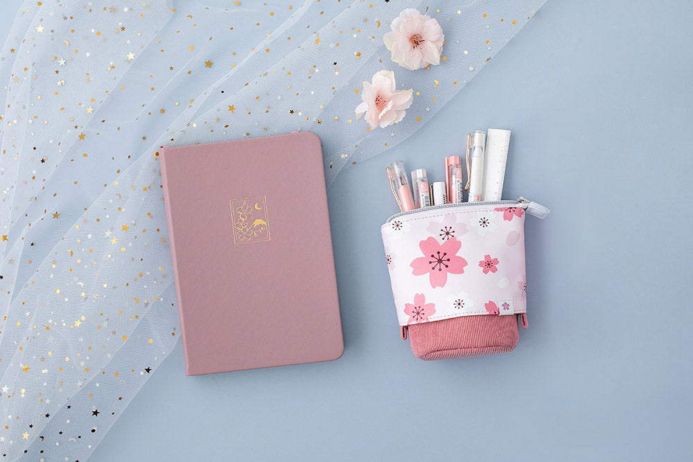 Blush pink sakura themed pop up pencil case and bullet journal notebook in soft blue background