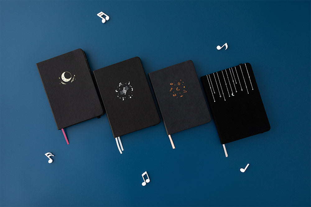 Tsuki Lunar Notes bullet journal with 3 other tsuki notebooks with music notes image on navy blue background