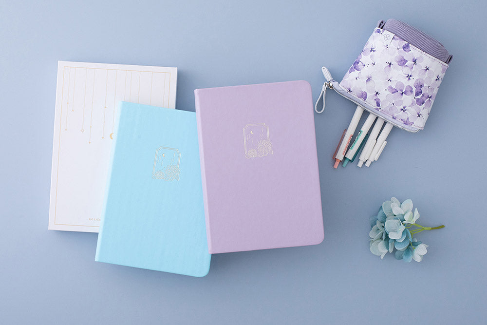 Tsuki Endless Summer Limited Edition Bullet Journals in Lilac Bloom and Petal Blue with eco-friendly gift box packaging and Tsuki Endless Summer Pop-Up Pencil case in Lilac Bloom and light blue hydrangea flowers on light blue background