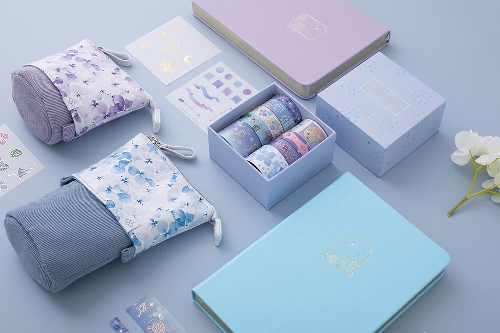 Tsuki Endless Summer collection Washi Tape set and free sticker sheets with Tsuki Endless Summer Limited Edition Bullet Journals and Tsuki Endless Summer pop-up pencil cases with white hydrangea flowers on lilac background