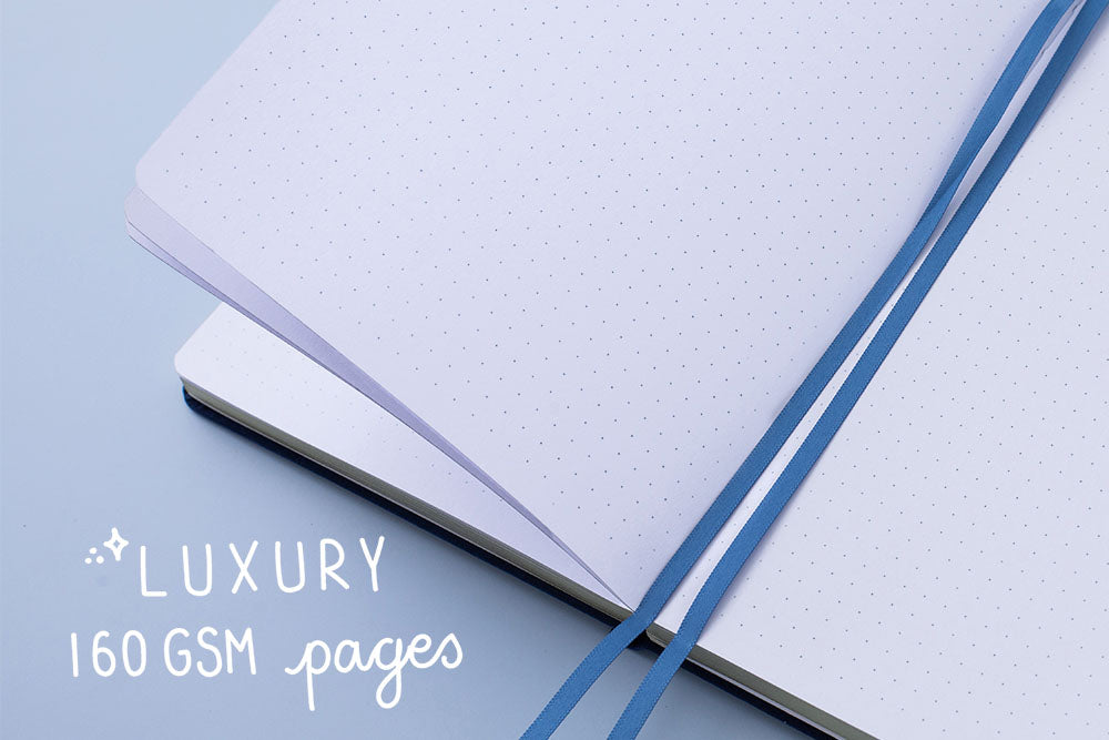 Deep blue soft velvet Tsuki Gentle Giant luxury edition bullet journal on open page with luxury 160GSM pages and two bookmark ribbons on blue background