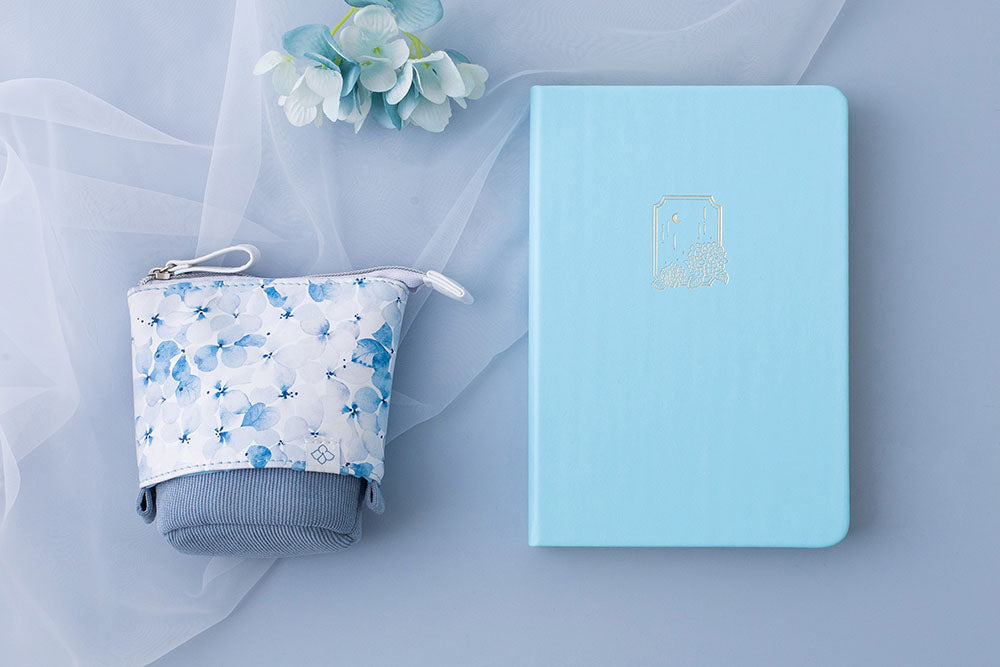 Tsuki Endless Summer Limited Edition Bullet Journal in Petal Blue with Tsuki Endless Summer Pop-Up Pencil case in light blue and light blue hydrangea flowers with netting on light blue background