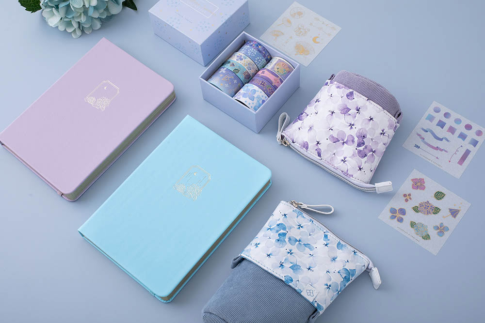 Tsuki Endless Summer Limited Edition Bullet Journals in Lilac Bloom and Petal Blue with Tsuki Endless Summer washi tape set and free sticker sheets with Tsuki Endless Summer Pop-Up Pencil cases with light blue hydrangea flowers at an angle on light blue background