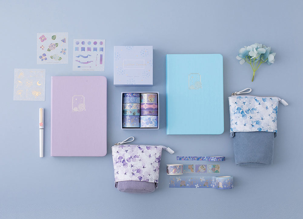 Tsuki Endless Summer Limited Edition Bullet Journals in Lilac Bloom and Petal Blue with Tsuki Endless Summer washi tape set and free sticker sheets with Tsuki Endless Summer Pop-Up Pencil cases with light blue hydrangea flowers and pen on light blue background